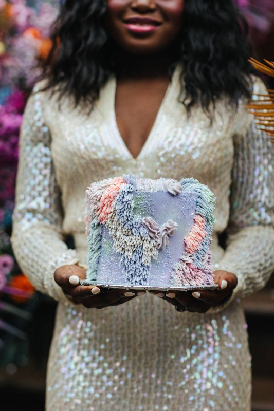 a jaw dropping iridescent wedding cake with pastel fringe and holographic embellishments is a lovely idea for a bright wedding
