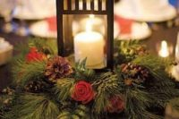 12 a lovely winter wedding centerpiece of an evergreen wreath with berries, red roses and pinecones plus a candle lantern in the center