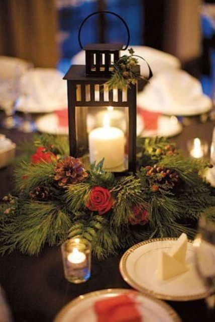 a lovely winter wedding centerpiece of an evergreen wreath with berries, red roses and pinecones plus a candle lantern in the center