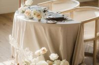 13 a beautiful neutral sweetheart table with a grey tablecloth, lush white blooms, tall and thin candles and grey menus