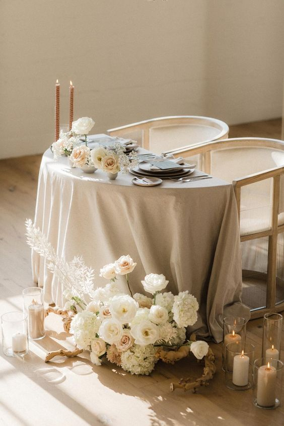 a beautiful neutral sweetheart table with a grey tablecloth, lush white blooms, tall and thin candles and grey menus