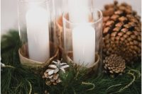 13 a pretty and cozy winter wedding centerpiece of evergreens, pinecones, candles in birch bark and some more lights around is amazing for a woodland or rustic celebration