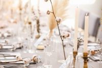 14 a beautiful neutral winter wedding tablescape with a grey tablecloth, cotton, dried blooms, candles and grass is awesome