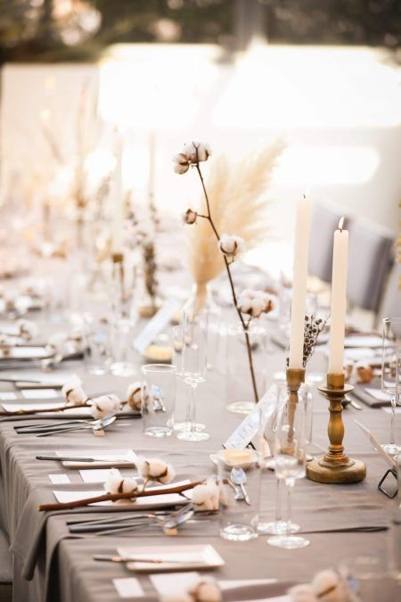 a beautiful neutral winter wedding tablescape with a grey tablecloth, cotton, dried blooms, candles and grass is awesome