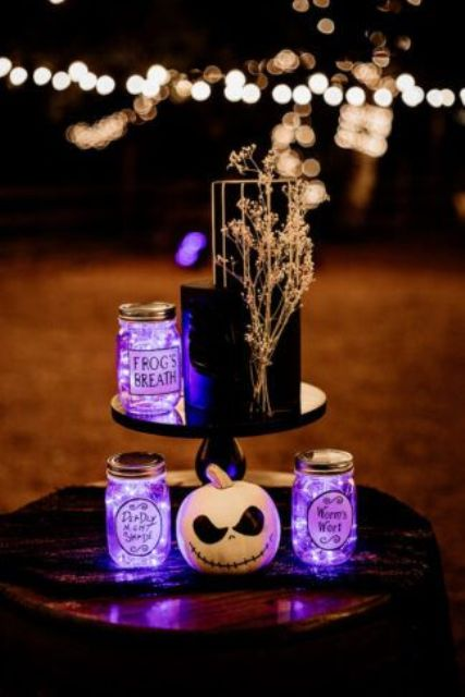 a black wedding cake decorated with dried blooms, jars with purple lights and a Jack Skellington pumpkin is wow