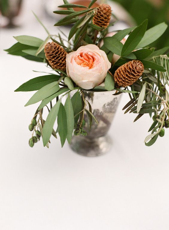 a pretty and simple winter wedding centerpiece of a shiny vase, greenery, blush peony roses and pinecones is a very cool and lovely idea
