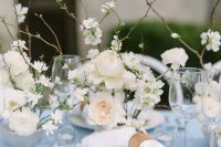 15 a beautiful winter wedding table setting with a pale blue tablecloth, refined plates, white blooms and branches plus candles