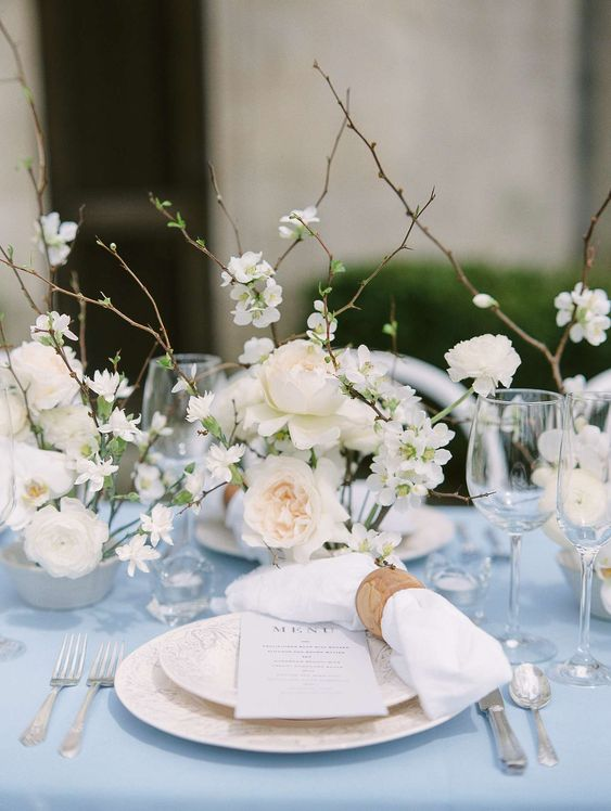 a beautiful winter wedding table setting with a pale blue tablecloth, refined plates, white blooms and branches plus candles