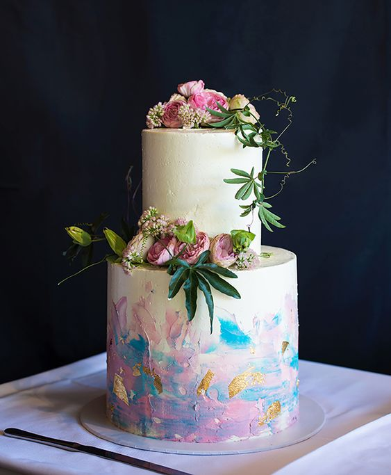 a white wedding cake with iridescent details and gold glitter, with fresh white and pink blooms and greenery