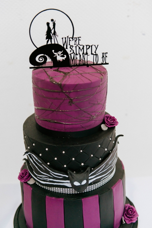 a bold black and purple wedding cake with various patterns, a black cake topper and sugar blooms is a stunning idea for your themed Nightmare Before Christmas wedding