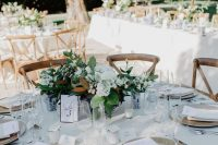 16 a chic neutral winter wedding tablescape with a white tablecloth and napkins, white blooms and greenery, candles and magnolia leaves