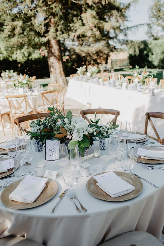 a chic neutral winter wedding tablescape with a white tablecloth and napkins, white blooms and greenery, candles and magnolia leaves