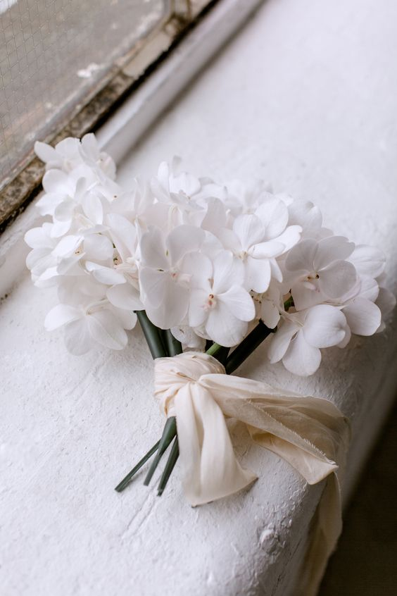 a chic one flower wedding bouquet in white, with neutral ribbons is a lovely idea for a minimalist and refined wedding
