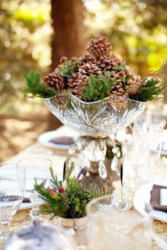 a pretty winter wedding centerpiece of a crystal bowl with pinecones, berries and evergreens is a delicate and cool idea for a woodland wedding