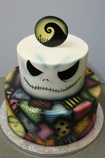 a bold Jack Skellington wedding cake with bright decor is a cool idea for a themed wedidng, it looks unusual and bold