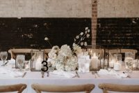 17 a chic winter wedding tablescape done in white, with candle lanterns, a lush white floral centerpiece, a black table number