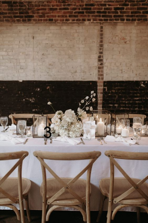 a chic winter wedding tablescape done in white, with candle lanterns, a lush white floral centerpiece, a black table number