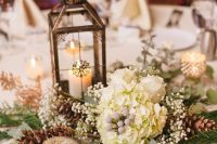 17 a refined winter wedding centerpiece of white hydrangeas, baby's breath, pinecones, a candle lantern and greenery is a cool idea to go for
