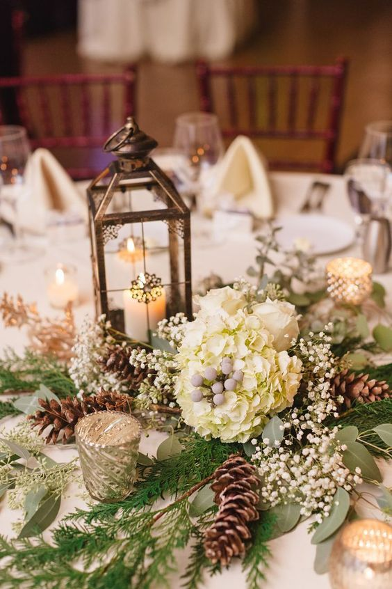 a refined winter wedding centerpiece of white hydrangeas, baby's breath, pinecones, a candle lantern and greenery is a cool idea to go for
