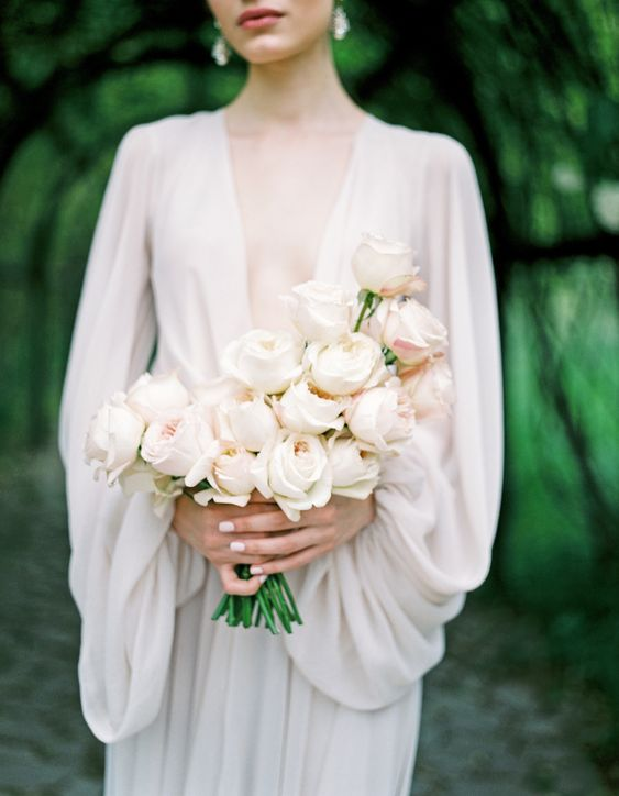 a dreamy and chic blush rose wedding bouquet with a catchy shape is a lovely idea for a modern or minimalist bride