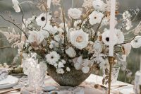 19 a frosty neutral winter wedding tablescape with a lush and large floral centerpiece, tall and thin candles and a pale pink table runner