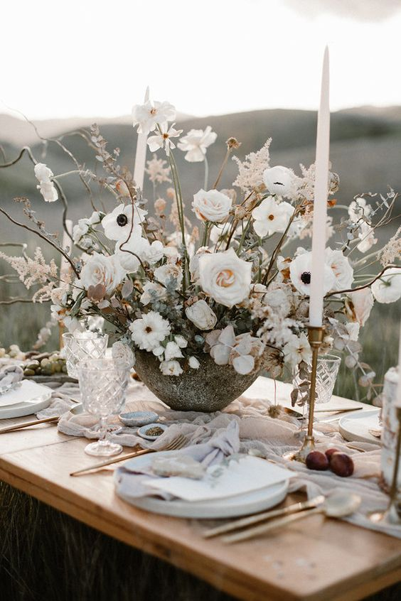 a frosty neutral winter wedding tablescape with a lush and large floral centerpiece, tall and thin candles and a pale pink table runner