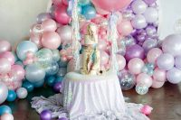 19 iridescent wedding decor with balloons, a wedding cake with iridescent geodes and gold edging, an iridescent tablecloth is wow