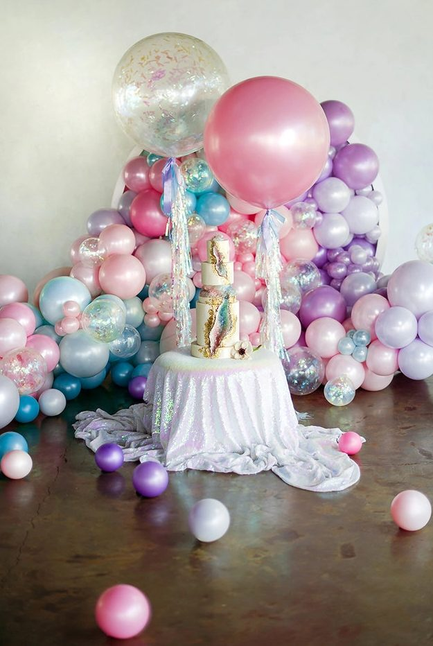 iridescent wedding decor with balloons, a wedding cake with iridescent geodes and gold edging, an iridescent tablecloth is wow