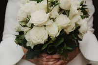 20 a gorgeous and classic white rose long stem wedding bouquet with green foliage is a stylish and cool solution for a modern or minimalist bride