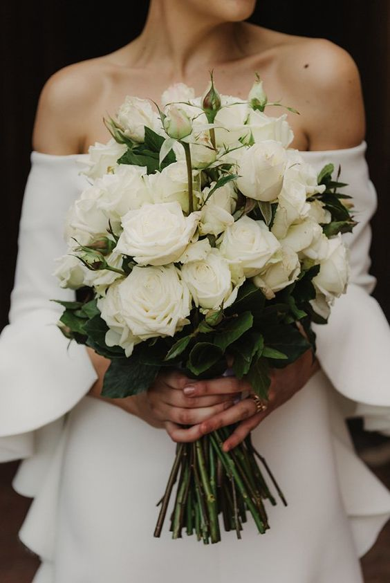a gorgeous and classic white rose long stem wedding bouquet with green foliage is a stylish and cool solution for a modern or minimalist bride