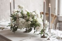 20 a light and ethereal refined winter wedding tablescape with grey candles and napkins, all white everything and white blooms and greenery