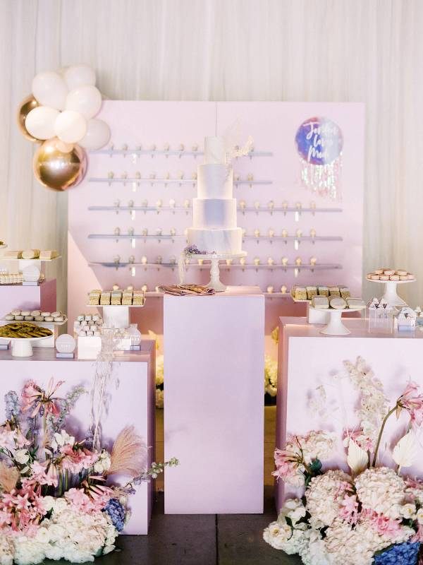 a pretty iridescent wedding sweets bar with ice cream, a marble cake, lilac stands and beautiful iridescent floral arrangements for decor