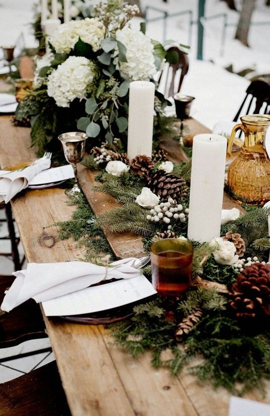 a rustic winter wedding centerpiece of a wooden bowl with pinecones, white roses, pillar candles and berries plus white floral arrangements on both sides