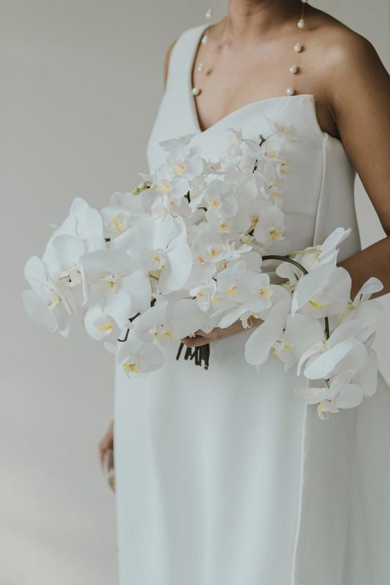 a lush and cascading white orchid wedding bouquet looks jaw-dropping with a minimalist wedding dress and lovely baroque pearl earrings