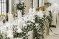 21 a luxurious winter wedding tablescape with white linens, white blooms, candles, greenery hanging down is a refined and beautiful idea to go for