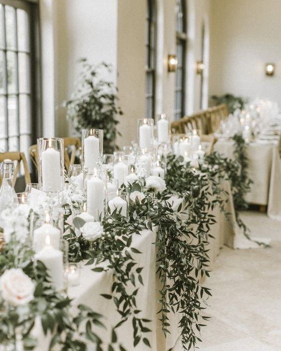 a luxurious winter wedding tablescape with white linens, white blooms, candles, greenery hanging down is a refined and beautiful idea to go for