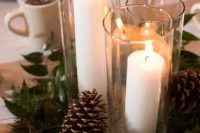 21 an inspiring winter wedding centerpiece of greenery, pinecones and pillar candles in tall glasses is a great idea for winter