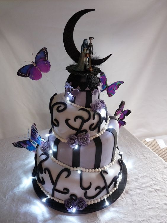 a lilac and black wedding cake with patterns, Jack and Sally cake toppers, a black crescent moon and lights is stunning
