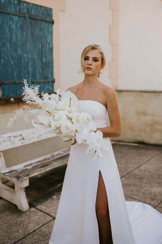 a lush white wedding bouquet with callas, orchids and some dried foliage, with a catchy shape and a cascading element is idea for a minimalist bride