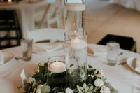 22 a minimalist winter wedding tablescape with a greenery and white flower wreath, candles, floating and usual ones and white linens