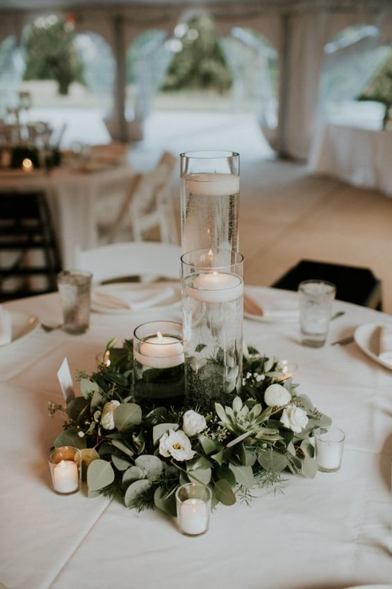 a minimalist winter wedding tablescape with a greenery and white flower wreath, candles, floating and usual ones and white linens