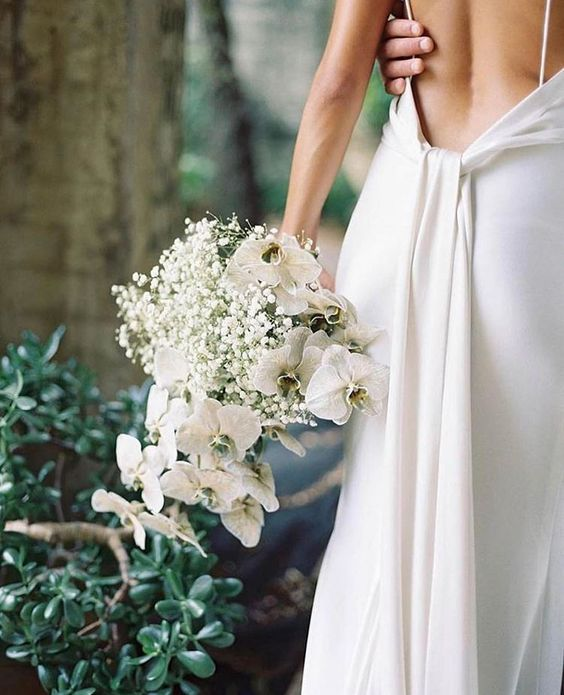 a minimalist white wedding bouquet of baby's breath and orchids is a pretty and cool idea for a minimalist bride and it looks catchy