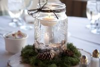 23 a simple wedding centerpiece of a wood slice, moss, pinecones and a jar with pebbles and a floating candle is an amazing rustic idea