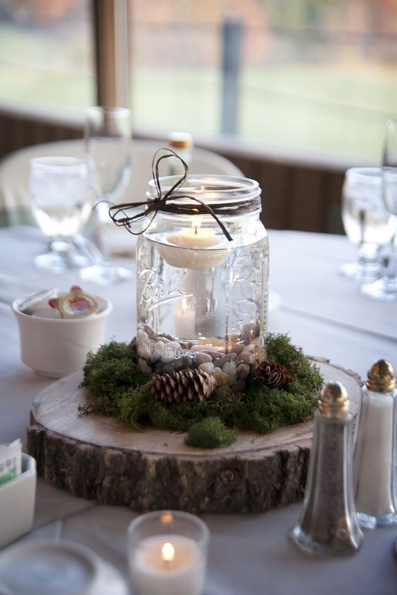 a simple wedding centerpiece of a wood slice, moss, pinecones and a jar with pebbles and a floating candle is an amazing rustic idea