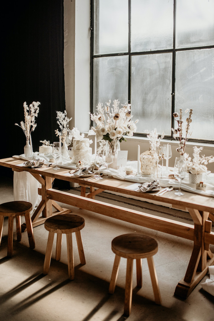 an organic winter wedding tablescape with white blooms, dried flowers and grasses, cotton buds and all white everything