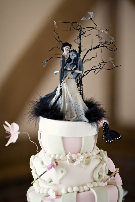 a neutral and pink wedding cake with themed cake toppers and a tree, butterflies and birds is a cool idea for a glam Tim Burton wedding