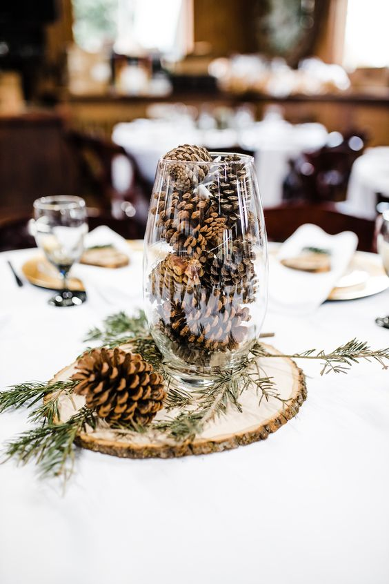 a simple rustic winter wedding centerpiece of a wood slice, a tall glass with pinecones and evergreens is veyr easy and fast to DIY