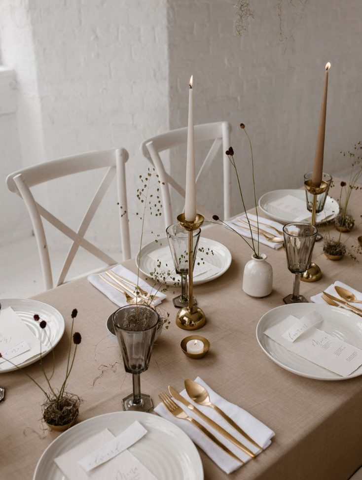 a warm colored minimalist winter wedding tablescape with a tan tablecloth, gold touches, grey glasses, dried flowers and all the rest done in white