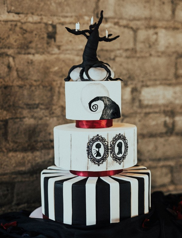 a Nightmare Before Christmas wedding cake in black and white, with stripes, with painted art amd a tree on top
