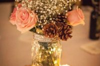 25 a shiny glam winter wedding centerpiece of white roses, baby's breath, pinecones, candles and a glitter wood slice is super cool